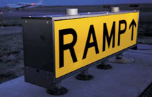 Runway ramp sign with prismatic translucent retroreflective material.